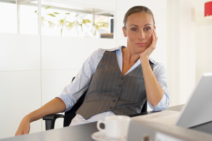 Single woman in front of computer with coffee